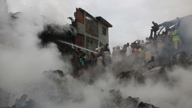 Rescue workers search for survivals after a plane crash in Lagos, Nigeria, Sunday, June 3, 2012. A passenger plane carrying more than 150 people crashed in Nigeria's largest city on Sunday, government officials said. Firefighters pulled at least one body from a building that was damaged by the crash and searched for survivors as several charred corpses could be seen in the rubble.(AP Photo/Sunday Alamba)