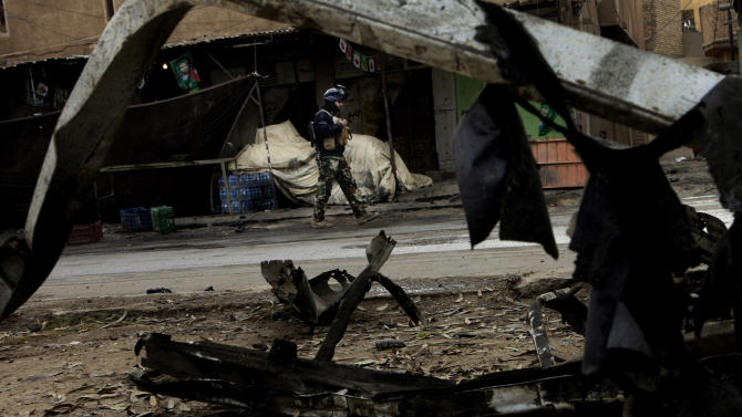 A policeman guards at the scene of a car bomb attack at a market in Dujail, 80 kilometers (50 miles) north of Baghdad, Iraq, Thursday, Jan. 17, 2013. Insurgents unleashed a string of bomb attacks mainly targeting Shiite Muslim pilgrims across Iraq on Thursday, killing and wounding scores of people, police said. (AP Photo/ Karim Kadim)