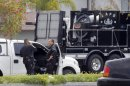 Los Angeles Police Department bomb squad officers gather at the site where police arrested a man after discovering explosive material in his car and potential explosive devices in his apartment Wednesday May 15, 2013 in Los Angeles. Four buildings have been evacuated and several blocks have been sealed off. Police are withholding the man's name until the investigation has concluded.(AP Photo/Nick Ut)