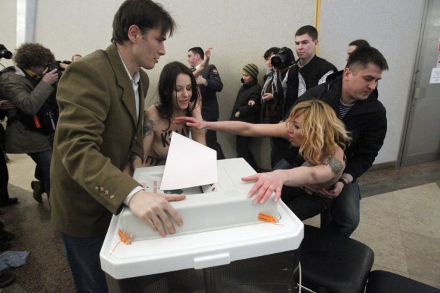 Polling station officials clash with topless members of Ukrainian feminist group FEMEN members at a polling station in Moscow on Sunday, March 4, 2012. Written on the bodies of the radically anti-Puti