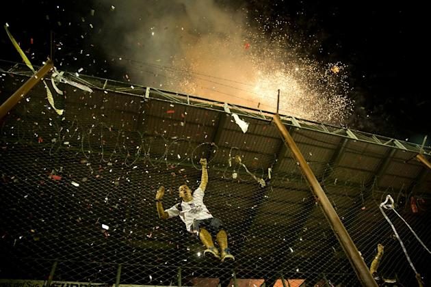 A fan of Argentina's Lanus climbs a fence as fireworks explode outside the stadium before the Copa Sudamericana final soccer match against Brazil's Ponte Preta in Buenos Aires, Argentina, Wedn