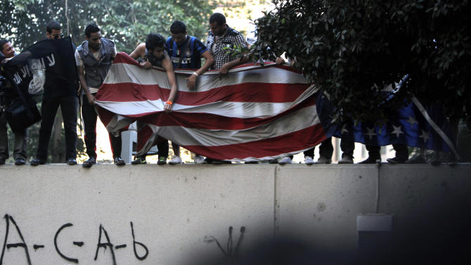 Protesters carry an American flag pulled down from the U.S. embassy in Cairo, Egypt, Tuesday, Sept. 11, 2012. Egyptian protesters, largely ultra conservative Islamists, have climbed the walls of the U.S. embassy in Cairo, went into the courtyard and brought down the flag, replacing it with a black flag with Islamic inscription, in protest of a film deemed offensive of Islam. (AP Photo/Nasser Nasser)