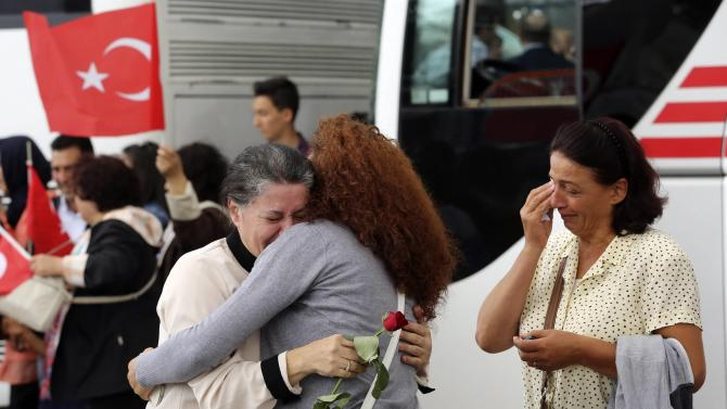 Employee at Turkey's consulate in Mosul is welcomed by her relatives at Esenboga airport in Ankara
