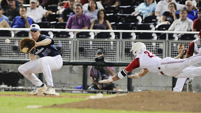 North Carolina State's Jake Armstrong, right, leaps but is out at first base against North Carolina first baseman Cody Stubbs, left, in the seventh inning of an NCAA College World Series elimination baseball game in Omaha, Neb., Thursday, June 20, 2013. (AP Photo/Eric Francis)