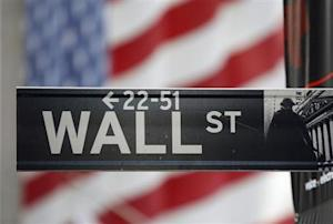 A sign for Wall Street is seen with a giant American flag in the background across from the New York Stock Exchange