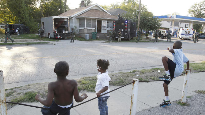In this Thursday, Aug. 23, 2012 photo, children watch from across the street after police raided a home in Washington Park, Ill., after a teenage girl told police she escaped from earlier in the week. The teen said she was held captive and sexually assaulted every day for two years. A  24-year-old man and his mother were arrested at the scene. They also recovered the teen's child, who she said is the result of rape by her captor. (AP Photo/Belleville News-Democrat, Zia Nizami)