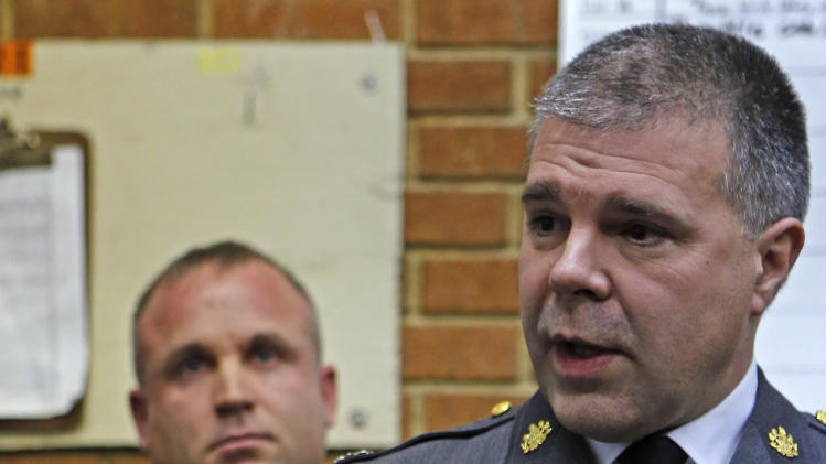 Pennsylvania State police Lt. George Bivens, right, talks during a news conference at the Geeseytown Fire Company about shootings along a nearby rural road that left four people dead and three Pennsylvania State troopers injured on Friday, Dec. 21, 2012 in Geeseytown, Pa. Pennsylvania state trooper Jeff Pettuci is at left. A man fatally shot a woman decorating for a children's Christmas party at a tiny church hall and killed two men elsewhere in the rural central Pennsylvania township Friday before he was fatally shot in a gunfight with state troopers. (AP Photo/Keith Srakocic)