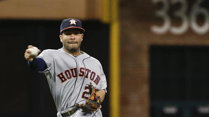 Houston Astros second baseman Jose Altuve spins in the air while deciding what to do with a slow roller hit by San Diego Padres' James Shields in the fifth inning of a baseball game Monday, April 27, 2015 in San Diego.   (AP Photo/Lenny Ignelzi))