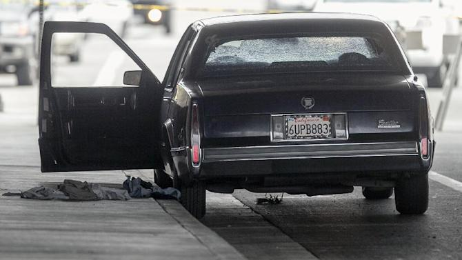 A vehicle riddle with bullet holes is part of  a crime scene on Red Hills Ave. under the 5 Interstate in Tustin, Calif., Tuesday, Feb. 19, 2013. Police say a chaotic 25-minute shooting spree through Orange County left a trail of dead and injured victims before the shooter killed himself.  There were multiple crime scenes in Tustin and Orange and many more victims who were shot at but unhurt, said Tustin Lt. Paul Garaven.  Tustin is about 35 miles southeast of downtown Los Angeles. (AP Photo/Damian Dovarganes)