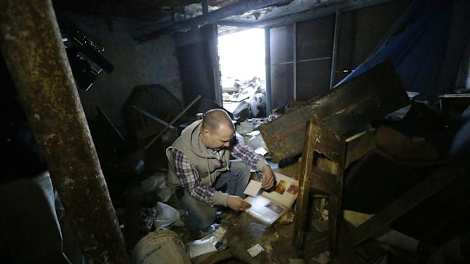 """In an April 3, 2013 photo, Tony Majka, who is also known as Tony Detroit on Instagram, looks over a photo album found inside an abandoned home in Detroit. Majka has been chronicling Detroit's blight epidemic in a unique and popular way. Under the name """"Tony Detroit,"""" he's been taking photos of the city's many abandoned structures with an iPhone and posting them on Instagram. The simple shots of Detroit's desolation has earned him better than 300,000 followers. (AP Photo/Carlos Osorio)"""
