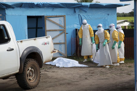 Health workers, wearing head-to-toe protective gear, prepare for work, outside an isolation unit in Foya District, Lofa County in this handout photo