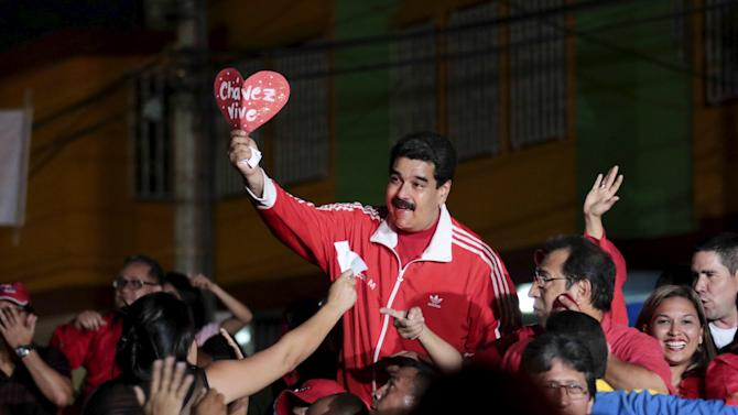 "Venezuela's President Nicolas Maduro (C) holds up a heart-shaped sign that reads, ""Chavez lives"", as he arrives for a campaign rally with pro-government candidates for the upcoming parliamentary elections in Barinas"