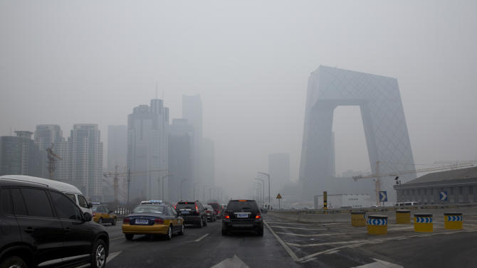 Cars clog in the traffic in Beijing's Central Business District on a hazy day, Friday, Feb. 21, 2014. A rare air pollution alert issued Friday in Beijing prompted health advisories and bans on barbeques, fireworks and demolition work, but fell short of the strictest measures which would include ordering half the city's cars off the streets. (AP Photo/Alexander F. Yuan)