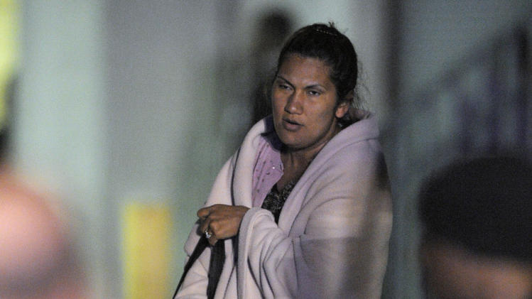 Carnival Triumph passenger Cecilia Alvarez stands wrapped in a blanket after departing the ship in Mobile, Ala., Thursday, Feb. 14, 2013. The ship with more than 4,200 passengers and crew members has been idled for nearly a week in the Gulf of Mexico following an engine room fire. (AP Photo/G M Andrews)