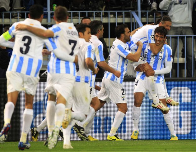 Malaga's Roque Santa Cruz is congratulated by team mates after scoring a goal against Porto during their soccer match at La Rosaleda stadium in Malaga