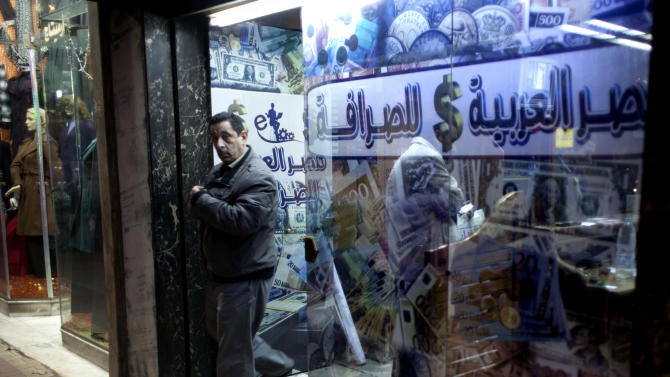 """FILE - In this Sunday, Jan. 6, 2013 file photo, an Egyptian man leaves after changing foreign currency at a currency exchange office, Arabic reads, """"Arabian Egypt for Exchange,"""" in Cairo, Egypt. Egypt's foreign currency reserves fell nearly 10 percent in a single month in January, according to figures released by the central bank Tuesday, Feb. 5, 2013, that provided stark new evidence of a dangerous deterioration in the economy amid political turmoil on the streets. (AP Photo/Nasser Nasser, File)"""