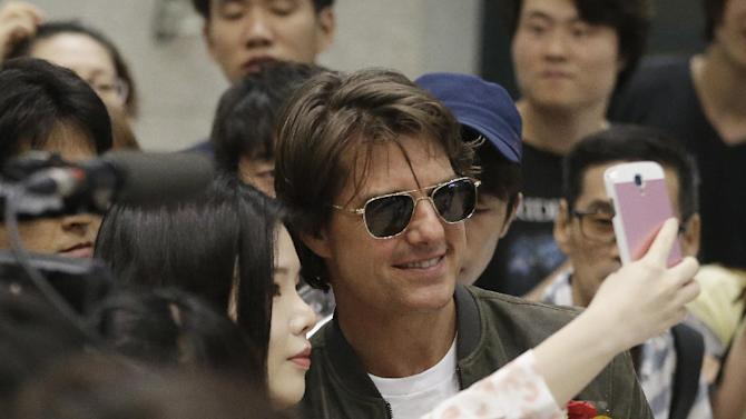 """Actor Tom Cruise takes pictures with a fan as he arrives to promote his latest movie """"Mission Impossible: Rogue Nation"""" at the Incheon International Airport, South Korea, Thursday, July 30, 2015. (AP Photo/Ahn Young-joon)"""