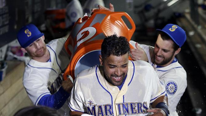 Seattle Mariners' Franklin Gutierrez is hit with a jug of water by teammates after hitting a home run to the win the game in the 10th inning of a baseball game Sunday, July 26, 2015, in Seattle. The Mariners won 6-5. (AP Photo/Elaine Thompson)