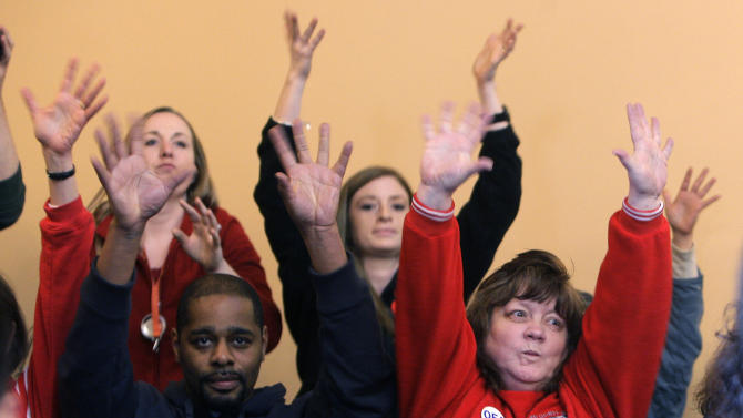Opponents of Senate Bill 5 silently clap in response to criticism of the bill during the floor debate for Senate Bill 5, Wednesday, March 2, 2011, in Columbus, Ohio. People in the gallery started silently clapping after being warned about outbursts and clapping during the debate. (AP Photo/Jay LaPrete)