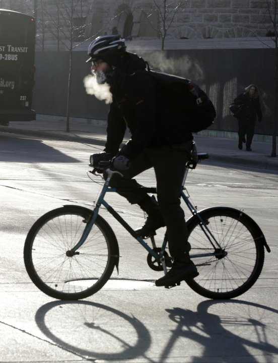 The breath of a bicyclist turns to steam and his beard frosts over as he bikes down the Nicollet Mall Tuesday, Jan. 22, 2013 in downtown Minneapolis where temperatures were in the double-digit, sub-ze