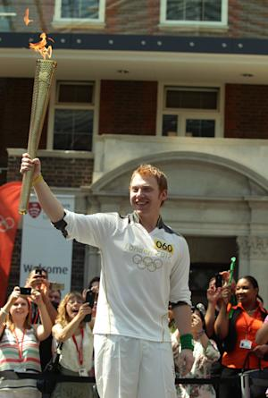 In this photo provided by LOCOG, British actor and torchbearer Rupert Grint holds the Olympic Flame at Middlesex University in London on Wednesday July 25, 2012. Opening ceremonies for the 2012 London Olympic Games will be held Friday, July 27.(AP Photo/LOCOG, Yui Mok)