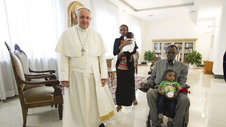 Pope Francis walks with Mariam Yahya Ibrahim, her husband and children during a private meeting at the Vatican