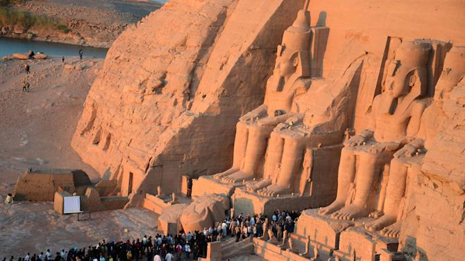 People visit the Great Temple of Ramses II, to observe the sun to send a beam of light into the ancient temple's dark inner chamber for over ten minutes in Abu Simbel, 870 kilometers (540 miles) south of Cairo, Egypt, Wednesday, Oct. 22, 2014. Hundreds of people visited the temple to watch the sun illuminate colossal statues, a rare 3,200-year-old astronomical ceremony that happens twice a year. (AP Photo/Ibrahim Zayed)