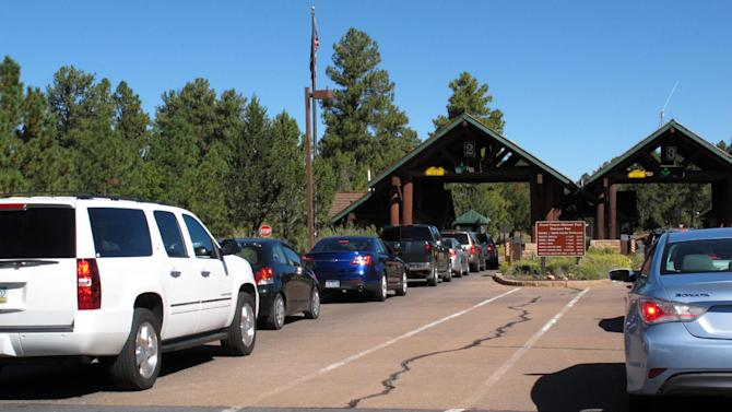 """In this Sept. 30, 2013, photo, cars line up at Grand Canyon National Park's South Rim entrance before the park was closed on Oct. 1 due to the partial government shutdown. Americans are finding that """"the government"""" entails a lot more than the stereotype of faceless D.C. bureaucrats cranking out red tape. (AP Photo/Felicia Fonseca)"""
