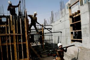 Palestinian laborers work on a construction site in…