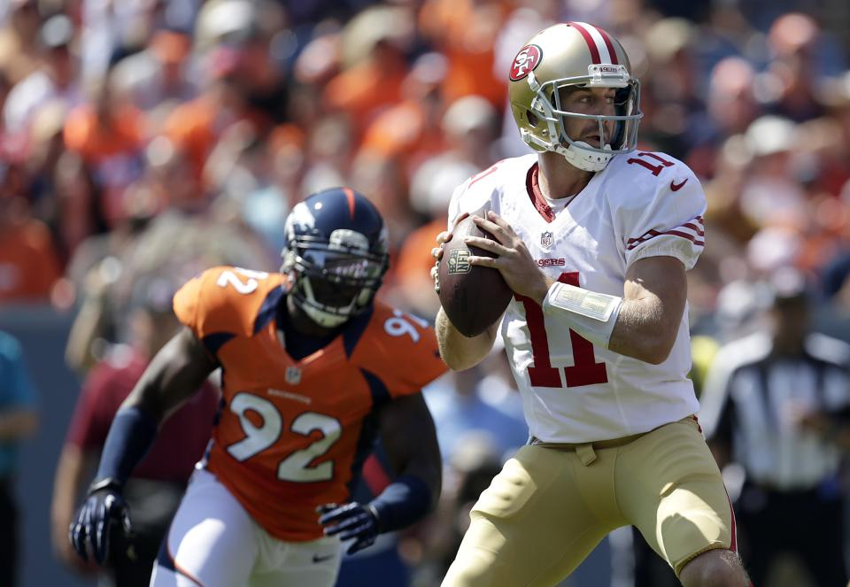 San Francisco 49ers quarterback Alex Smith (11) passes as Denver Broncos defensive end Elvis Dumervil (92) rushes during the first quarter of an NFL preseason football game in Denver, Sunday, Aug. 26, 2012. (AP Photo/Joe Mahoney)