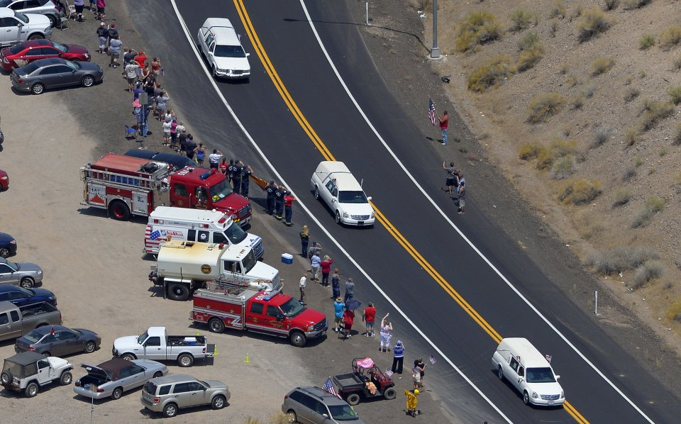 Three of a procession of 19 hearses drives through the desert, Sunday, July 7, 2013, near Morristown, Ariz. The elite crew of firefighters were overtaken by the out-of-control blaze as they tried to protect themselves from the flames under fire-resistant shields last Sunday. (AP Photo/Mark J. Terrill)