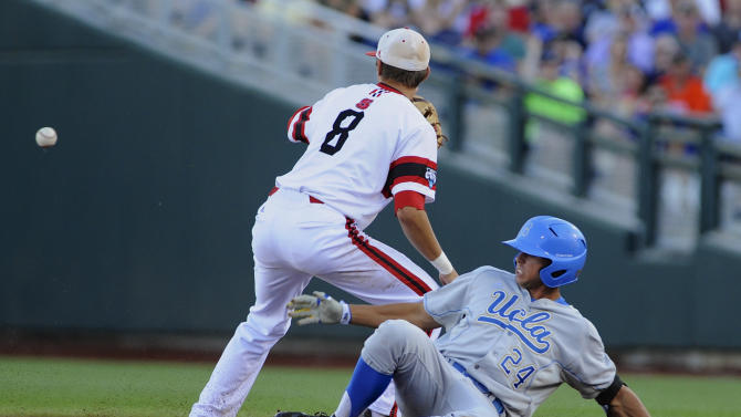 UCLA's Brian Carroll reaches second base ahead of the throw to North Carolina State shortstop Trea Turner after hitting a double in the second inning of an NCAA College World Series game in Omaha, Neb., Tuesday, June 18, 2013. (AP Photo/Eric Francis)
