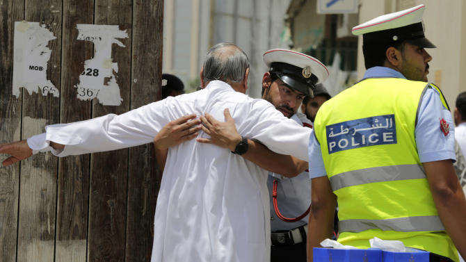 "FILE- In this Friday, June 5, 2015 file photo, Bahraini community police officers search worshipers outside a Shiite Muslim mosque ahead of mid-day prayers in Manama. Bahraini authorities say two policemen have been killed and many injured in a bomb attack south of the capital. The Interior Ministry said on its Twitter feed on Tuesday, July 28, 2015 that the officers were killed in a ""terror blast"" in the largely Shiite community of Sitra. (AP Photo/Hasan Jamali, File)"