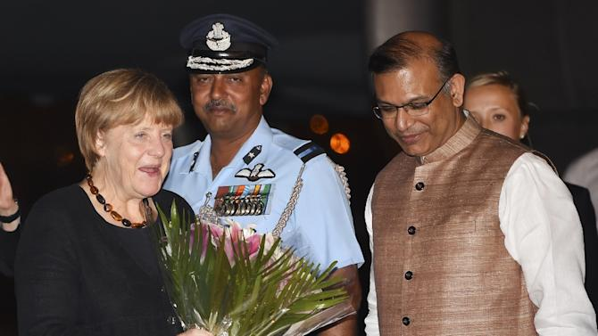 German Chancellor Angel Merkel smiles and holds flowers as she greets Indian officials after arriving at the airport in New Delhi on October 4, 2015 for a two-day visit to India