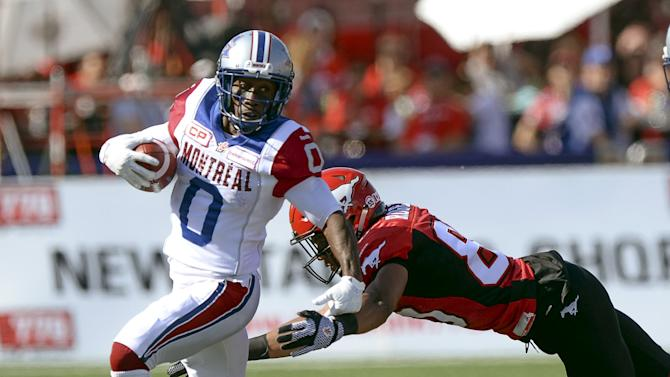 Montreal Alouettes' Logan outruns Calgary Stampeders' Rogers during a CFL football game in Calgary