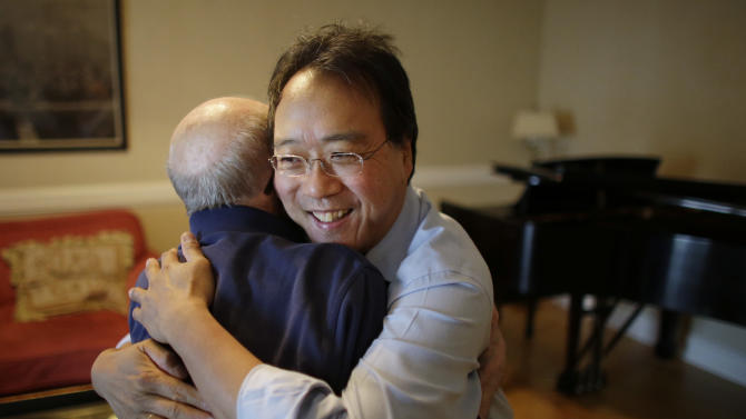 Cellist Yo-Yo Ma, right, greets Holocaust survivor George Horner in a rehearsal room at Symphony Hall Tuesday afternoon, Oct. 22, 2013, in Boston. The 90-year-old pianist will make his orchestral debut with Ma Tuesday night, where they will play music composed 70 years ago at the Nazi prison camp where Horner was imprisoned. (AP Photo/Steven Senne)
