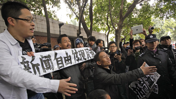 "Supporters of Southern Weekly newspaper argue with police officers during a protest outside the headquarters of the newspaper in Guangzhou, Guangdong province, China Wednesday, Jan. 9, 2013. Communist Party-backed management and rebellious editors at the influential weekly newspaper have defused a high-profile standoff over censorship that turned into a test of the new Chinese leadership's tolerance for political reform. The banner reads ""Press freedom reflect people's view."" (AP Photo/Vincent Yu)"
