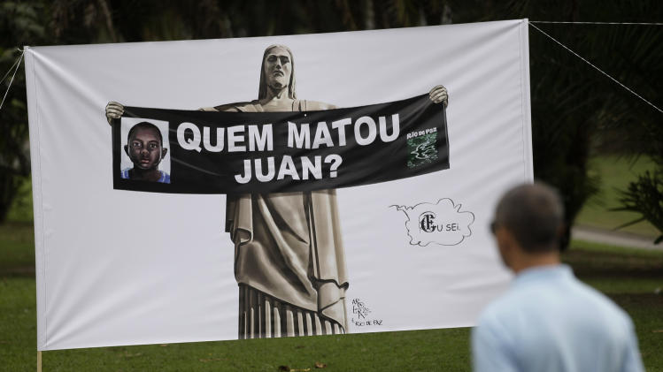 "In this photo taken Tuesday, July 19, 2011, a man looks at a sign depicting the statue Christ the Redeemer holding a banner with a picture of Juan Moraes and the question in Portuguese: ""Who killed Juan?"" during a protest in Rio de Janeiro, Brazil. The Brazilian city that will host the 2016 Olympic Games has one of the deadliest police forces on the planet and Juan Moraes' killing is an example of how serious the problem is. In the last five years, officers in Rio have killed on average 3.5 people per day, according to an Associated Press analysis of police data. The four police officers suspected in Moraes' death have 37 on-duty killings among them, according to police records. (AP Photo/Silvia Izquierdo)"