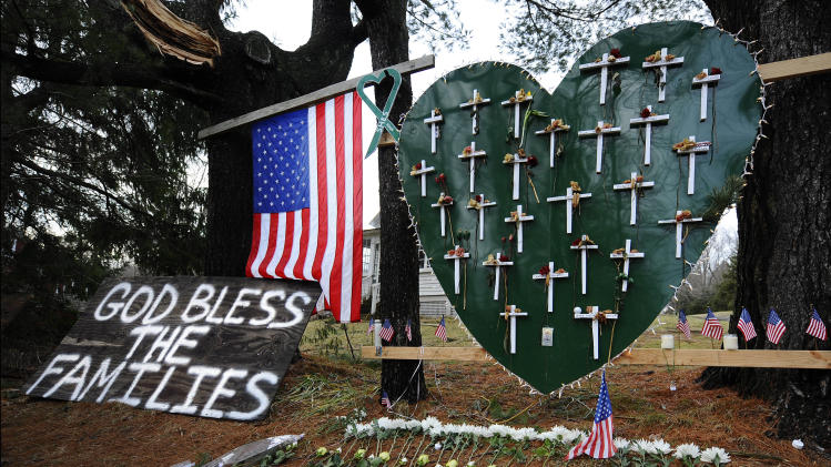 A memorial is displayed in a yard near the Sandy Hook Elementary School on the one-month anniversary of the mass shooting that left 26 dead, including 20 children in Newtown, Conn., Monday, Jan. 14, 2013. (AP Photo/Jessica Hill)