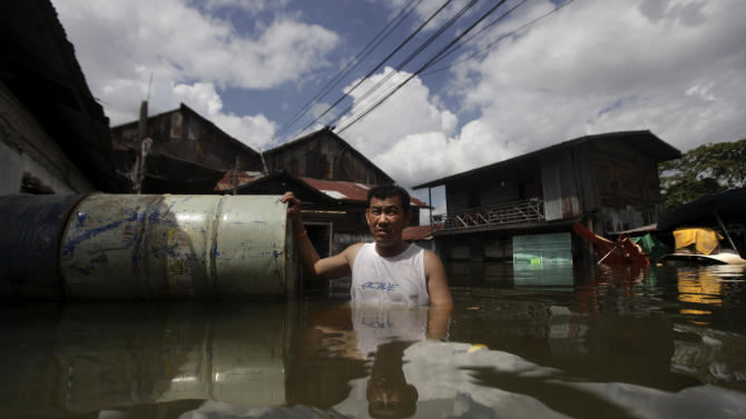 A Thai man leaves his submerged house as the swollen Chao Phraya River overflows in Bangkok, Thailand, Saturday, Oct. 29, 2011. Defenses shielding the center of Thailand's capital from the worst floods in nearly 60 years mostly held at critical peak tides Saturday, but areas along the city's outskirts remained submerged along with much of the countryside. (AP Photo/Altaf Qadri)