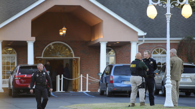 "Law enforcement personnel wait outside the funeral home as people pay their respects to Charles Albert ""Chuck"" Poland, the 66 year old bus driver who gave his life to save the children on his bus, Saturday, Feb. 2, 2013 in Slocumb, Ala. As the police standoff with an Alabama man accused of holding a 5-year-old boy hostage continued Saturday, a nearby community prepared to bury, Poland, the beloved bus driver who was shot to death trying to protect children on his bus when the episode began days earlier (AP Photo/AL.com, Joe Songer) MAGS OUT"