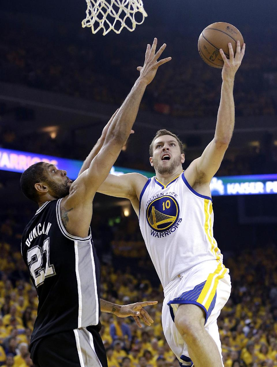 Golden State Warriors forward David Lee (10) goes for a lay-up over San Antonio Spurs forward Tim Duncan (21) in the first quarter of Game 6 of a Western Conference semifinal NBA basketball playoff series in Oakland, Calif., Thursday, May 16, 2013. (AP Photo/Marcio Jose Sanchez)