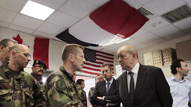 French Defense Minister Jean-Yves Le Drian, right, listens to a French military official with the NATO- forces ahead of a press conference in Kabul, Afghanistan, Wednesday, July 18, 2012. France's defense minister says that while Paris opposes capital punishment it will respect an Afghan military court's decision to sentence an Afghan soldier to death for killing four French troops. (AP Photo/Musadeq Sadeq)