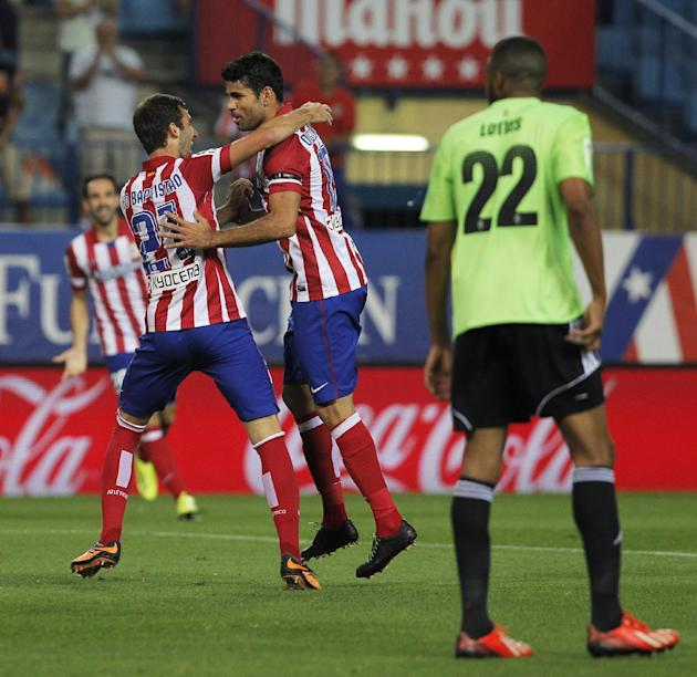 Atletico de Madrid's Diego Costa from Brazil, second left, celebrates his goal with Leo Baptistao, left, during a Spanish La Liga soccer match against Osasuna at the Vicente Calderon stadium in Madrid