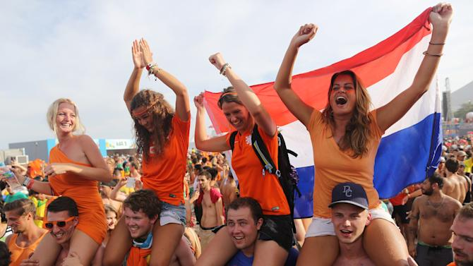 Dutch soccer fans celebrate their team's victory after they watched the World Cup round of 16 match against Mexico on a live telecast inside the FIFA Fan Fest area on Copacabana beach in Rio de Janeiro, Brazil, Sunday, June 29, 2014. The Netherlands staged a dramatic late comeback, scoring two goals in the dying minutes to beat Mexico 2-1 and advance to the World Cup quarterfinals. (AP Photo/Leo Correa)