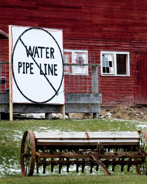 A large sign states the property owners stand on a purposed pipeline to prove drinking water to households on Carter Road in Dimock, Pa. in this photo taken Dec. 21, 2010.  Residents in suburban Texas and rural Pennsylvania are living with the nastiness and rancor erupting in communities nationwide over the volatile issue of hydraulic fracturing, a form of gas drilling. (AP Photo/Ralph Wilson)