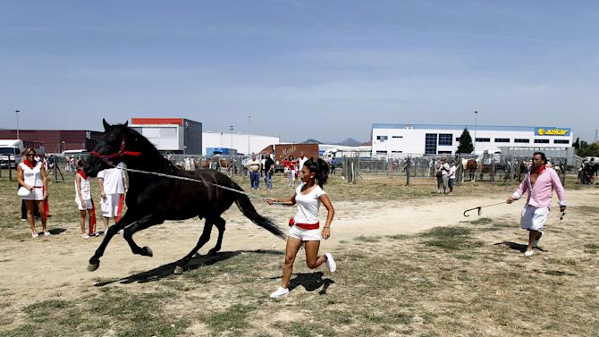 A woman dressed in traditional festival colours runs next to a horse during a horse trading fair on the second day of the San Fermin festival in Pamplona