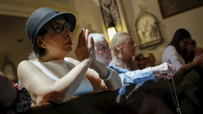 People pray while they attend the last mass at Church of Our Lady Peace in New York