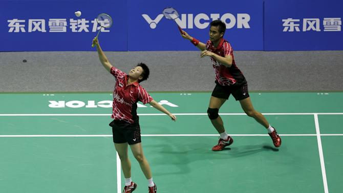 Natsir of Indonesia hits a return next to her partner Ahmad during their mixed doubles semi-final match against Xu and Ma of China at the 2015 Badminton Asia Championships, in Wuhan