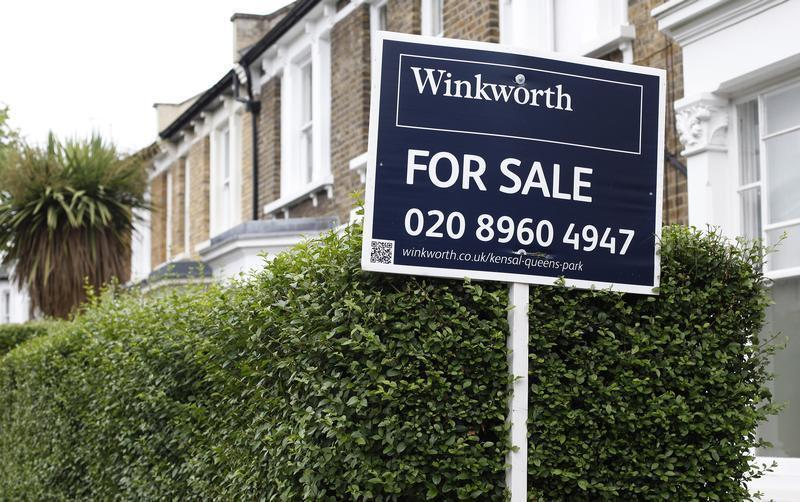 An estate agent's sign is posted outside a terraced house in north London
